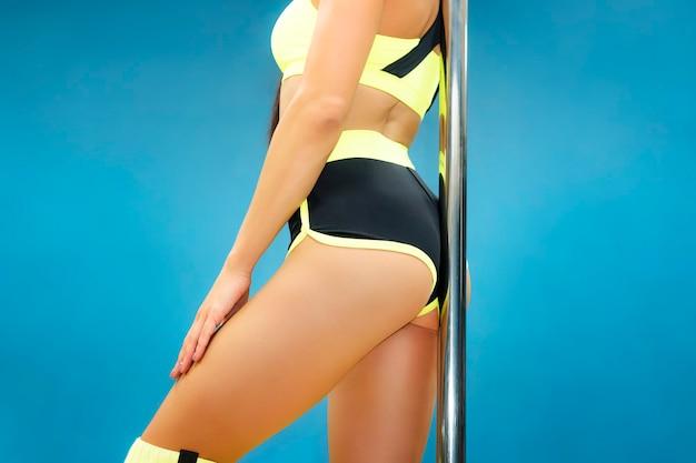 青い背景で魅力的な女性のポールダンストレーナーのクローズアップ。お尻でポールに触れるセクシーな衣装のポールダンサー。青の運動体操選手の美しい体。エキサイティングなフィットネス。