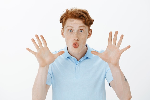 誰かを嘲笑し、空の手を示し、愚かなふくれっ面をしている魅力的な面白い赤毛の男のクローズアップ