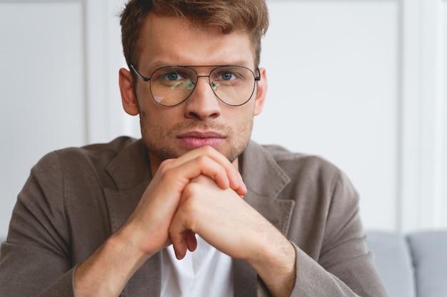 手で頭を支え、真剣な表情で見ている眼鏡の魅力的な紳士のクローズアップ