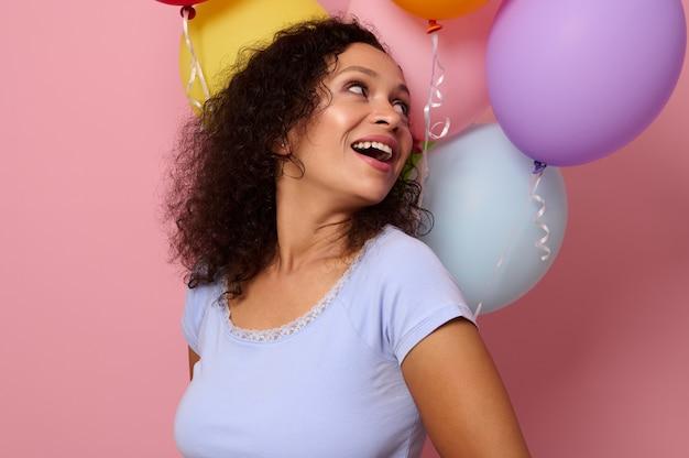 コピースペースとピンク色の背景に膨らんだカラフルな気球を肩越しに見ている美しい歯を見せる笑顔で笑っている魅力的な幸せな陽気な混血の女性のクローズアップ