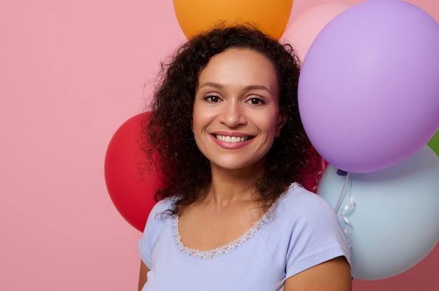 魅力的な幸せな陽気な混血の女性のクローズアップは、コピースペースとピンク色の背景に膨らんだカラフルな気球に対してポーズをとって、カメラを見て美しい歯を見せる笑顔で笑っています。