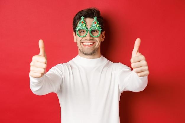 パーティーグラスと白いセーターの魅力的な幸せな男のクローズアップ、承認と笑顔で親指を示し、赤い背景の上に立っています。