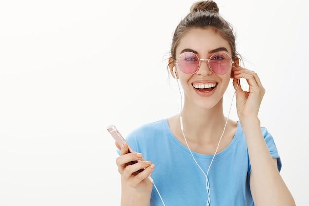 音楽を聴いて、イヤホンで歌を楽しんで、スマートフォンを持ってサングラスで魅力的な現代女性のクローズアップ