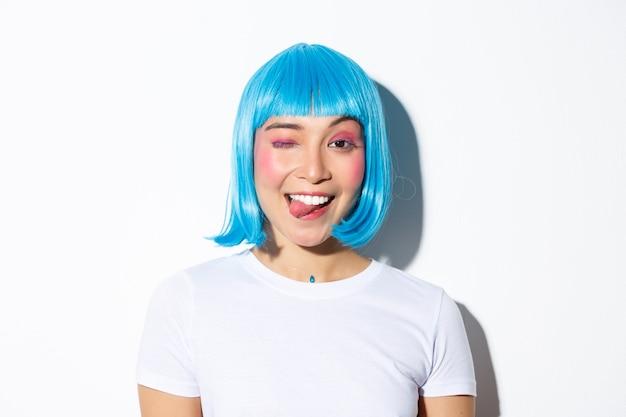 青いかつらで魅力的なパーティーガールのクローズアップ、舌を示し、幸せにウインク、ハロウィーンを祝って、立っています。