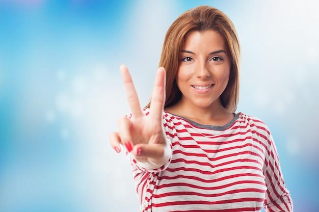 평화 기호를 보여주는 매력적인 여자의 클로즈업