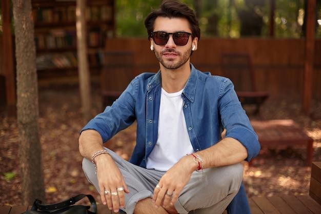 Крупный план привлекательного молодого бородатого мужчины в солнечных очках, позирующего над городским садом, сидящего со скрещенными ногами, опираясь руками на колени