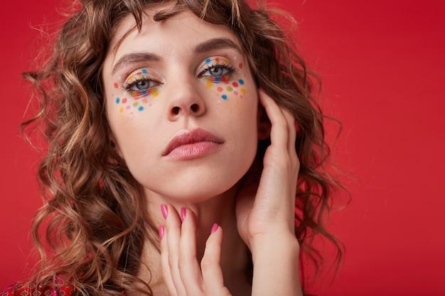 Крупный план привлекательной молодой женщины с романтической прической и праздничным макияжем, держащей руку на шее и выглядящей мягкой, стоя