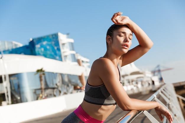 Крупный план привлекательной молодой женщины фитнеса, опираясь на поручень