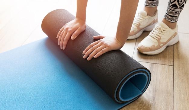 Крупный план привлекательной молодой женщины, складывающей синий коврик для йоги или фитнеса после тренировки дома в гостиной.