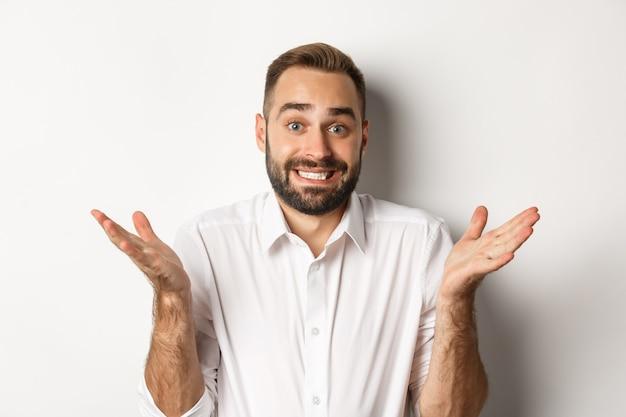 ぎこちないマネージャーのクローズアップは、白い背景の上に無知に立って、肩をすくめて、申し訳ない表情で笑っています。