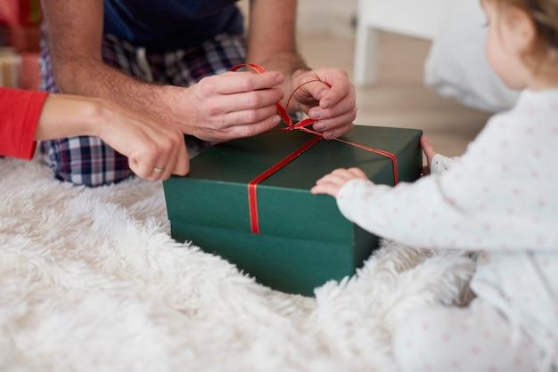 부모와 함께 크리스마스 선물을 여는 아기의 클로즈업