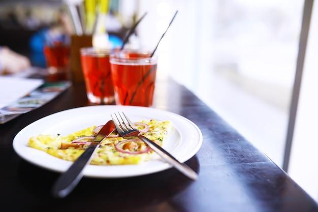 Крупный план пиццы с беконом, апельсинового сока в стакане на столе в кафе в ресторане