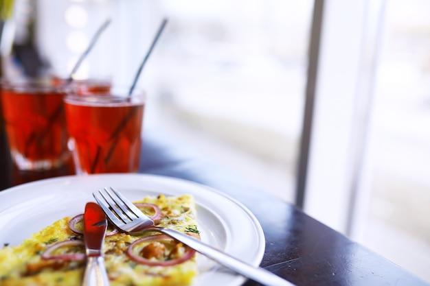 베이컨 피자 클로즈업, 레스토랑의 카페 테이블에 있는 유리잔에 담긴 오렌지 주스