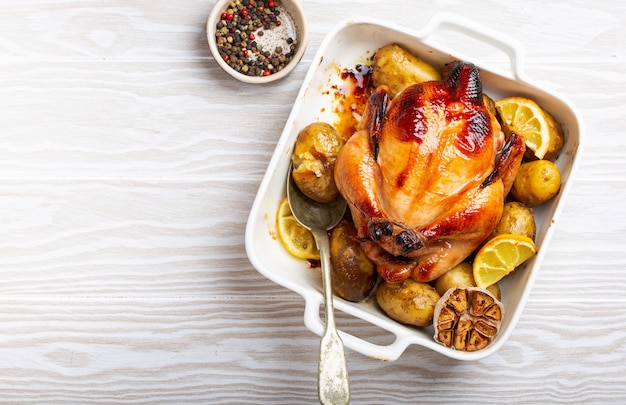 Крупный план запеченной или жареной цельной сочной хрустящей органической курицы с картофелем, чесноком, лимоном в белой запеканке с сервировочной ложкой на белом деревянном фоне, вид сверху и место для текста