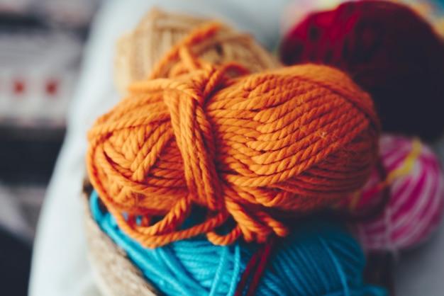 丸い籐のかごの中の編みウールのボールのクローズアップ。編み物用のウール糸の色とりどりのボール。ふわふわの羊毛のボールの山。編み物や針編み用の毛糸。