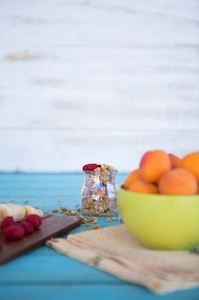 Close-up of banana slices; strawberries; peach and oats on blue wooden surface