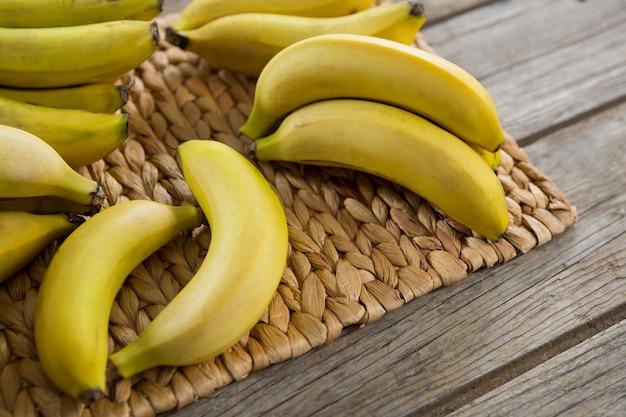 木製のテーブルのプレースマットに保管されているバナナのクローズアップ