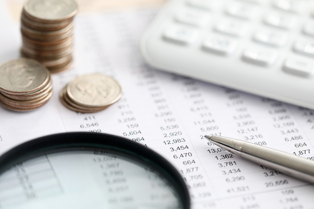 銀行取引明細書、電卓、コインとペンのスタックの拡大図。銀行の従業員がレポートを作成