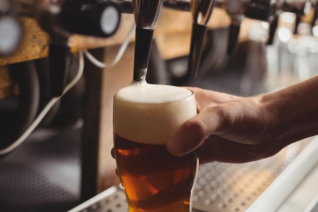 Крупный план барного тендера, разливающего пиво из барного насоса