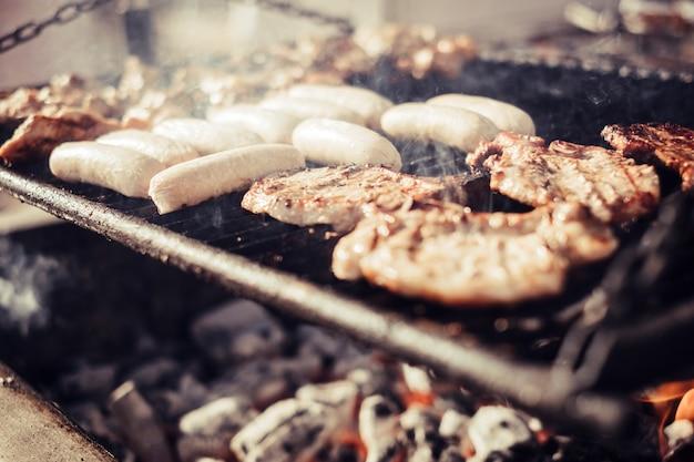 火とカーボンでバーベキューミートグリルのクローズアップ。屋外の友情のお祝いでイータにおいしい料理