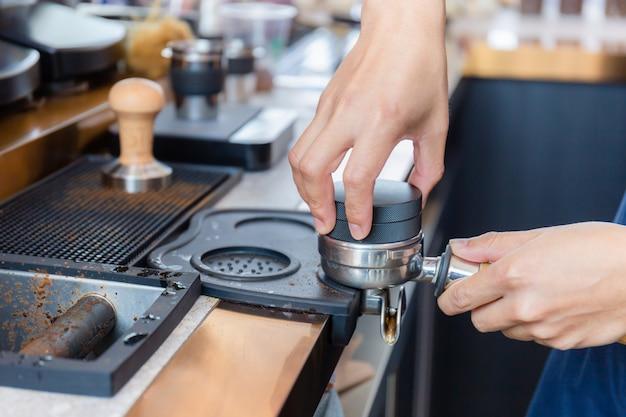Крупным планом руки бариста приготовления кофе на машине