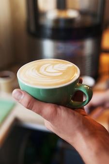 芳香族カプチーノを保持しているバリスタのクローズアップ。コーヒーの販売の準備ができています。一杯のコーヒーを保持している男性の手。