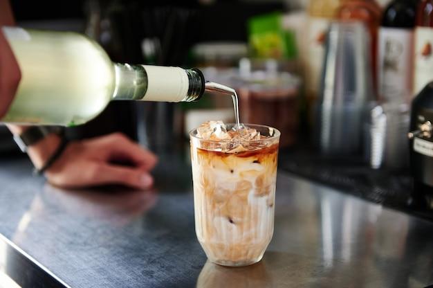 Крупный план бариста, готовящего освежающий ледяной напиток с кофеином, наливает жидкий коктейль в стакан с ледяным напитком латте