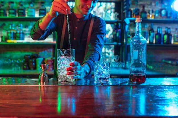 バーテンダーのクローズアップは、色とりどりのネオンライトでアルコールカクテルの準備を終了します