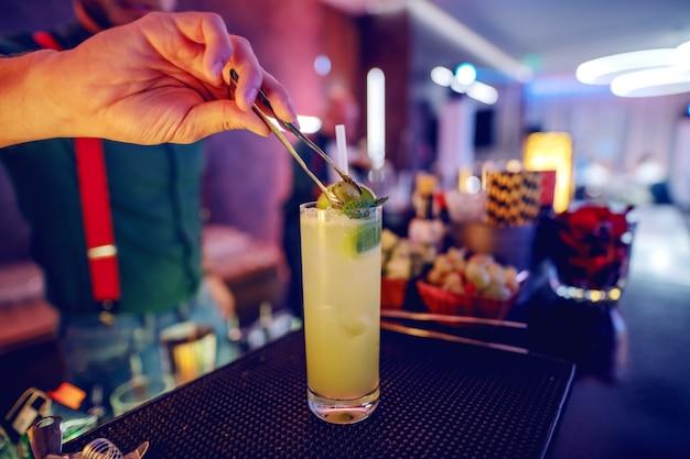 カクテルをグラスにオリーブを入れてバーテンダーのクローズアップ。