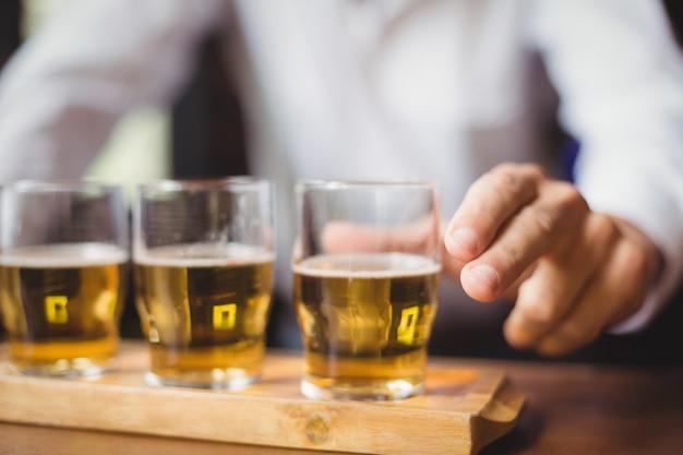 バーのカウンターでウイスキーショットグラスを保持しているバーテンダーのクローズアップ