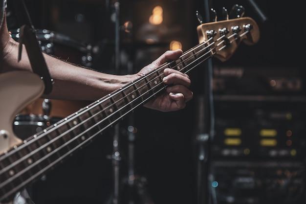 흐릿한 어두운 배경 복사 공간에 베이스 기타를 닫습니다.