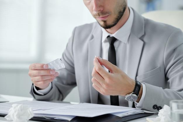 Крупный план бородатого бизнесмена в сером костюме, сидящего за столом с документами и принимающего таблетки от простуды