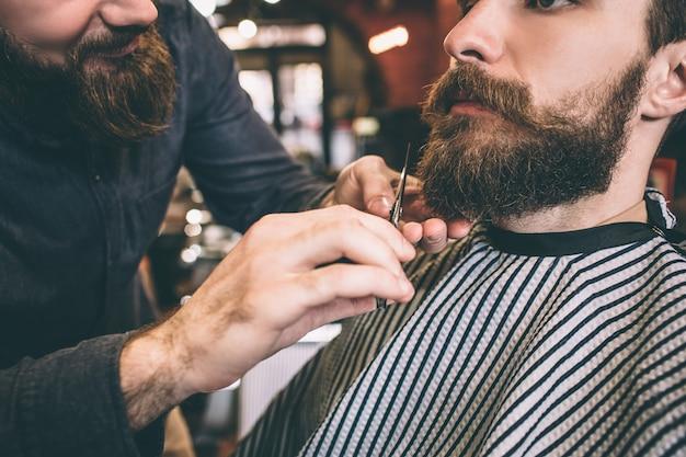 Крупным планом бородатый парень. парикмахер подстригает часть своей бороды. процесс медленный, но уверенный и стоит того. вырезать вид.