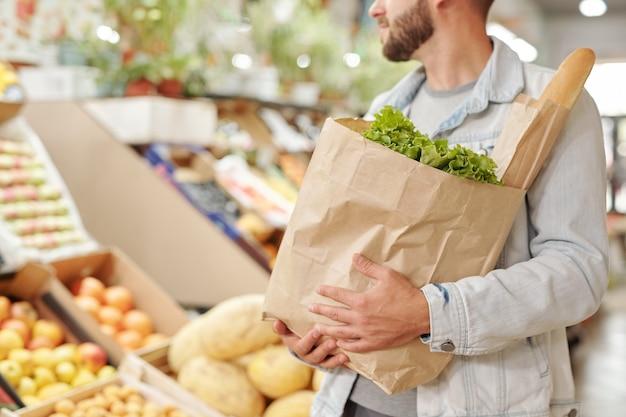 食品市場で新鮮な製品の完全な紙袋を運ぶデニムジャケットのひげを生やした男のクローズアップ