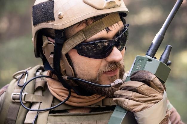 군사 작전 중 동료에게 메시지를 보내는 동안 라디오를 사용하여 헬멧과 선글라스를 쓴 수염 난 군인의 클로즈업
