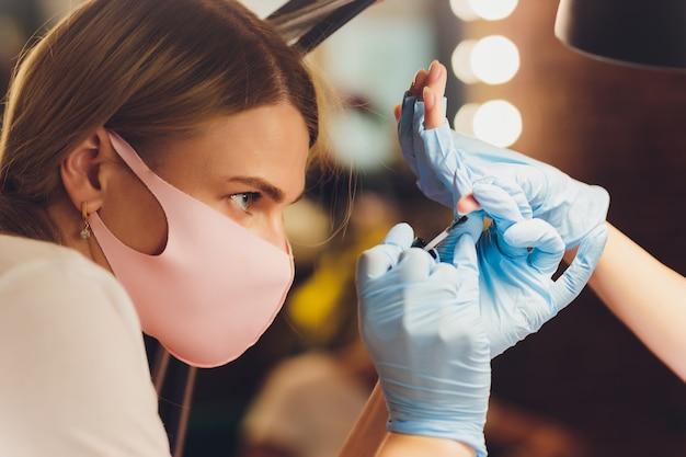 カラフルなニスを適用する美容師のクローズアップ。指にマニキュアを塗るブラシでマニキュアを塗る。ビューティーサロンのマニキュアネイルアプリケーター。ビューティーサロンのニス。