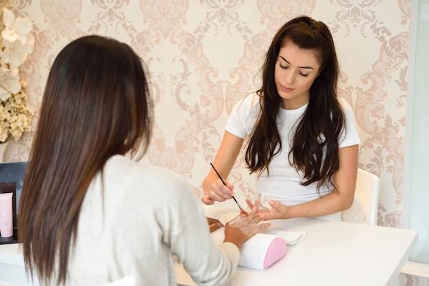 ブラシを使用して女性の手にクリームを適用する美容師のクローズアップ。