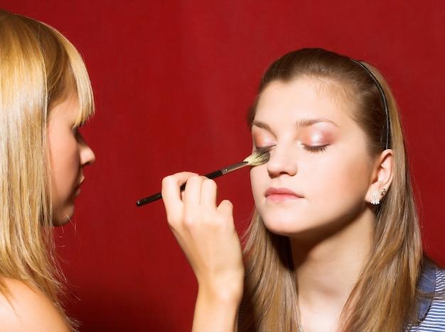 Закройте косметолога, создающего макияж для молодых женщин в салоне красоты.