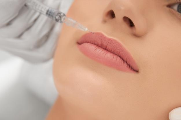 Крупным планом косметолог в белых резиновых перчатках делает инъекцию для увеличения губ профессиональными препаратами
