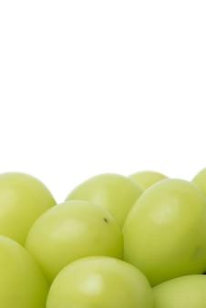 白い背景に分離されたシャインマスカット緑のブドウの美しい束のクローズアップ、クリッピングパスが切り取られました。