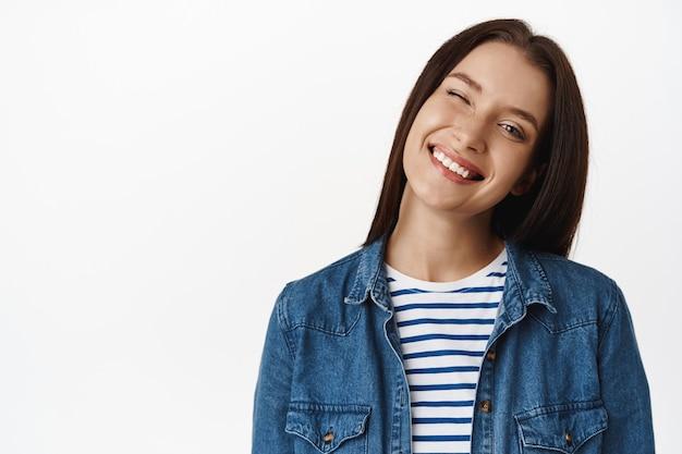 ウィンク、笑顔、白い完璧な歯、のんきな幸せな感情、白い服を着て立っている美しい大人の女性モデルのクローズアップ。