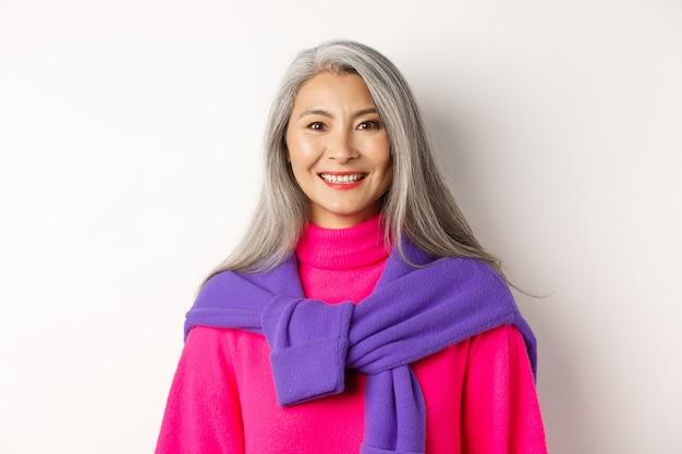 トレンディなピンクのセーター、カメラで陽気な笑顔、白い背景の上に立っている美しいアジアの年配の女性のクローズアップ。