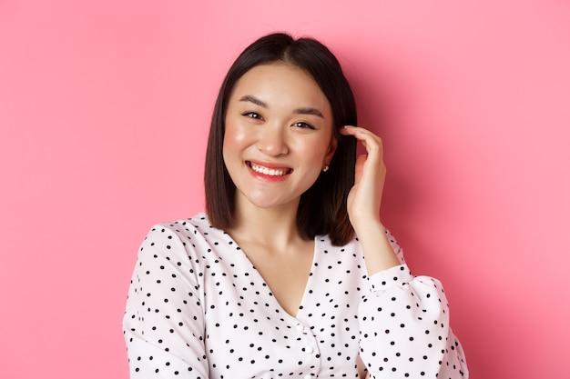 아름 다운 아시아 여자의 근접 행복 미소, 새로운 헤어 스타일을 만지고, 핑크 위에 서 서