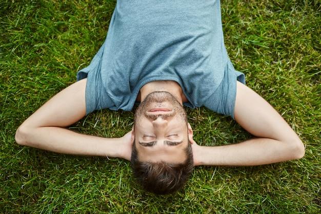 Крупным планом красивый бородатый зрелый кавказский мужчина в синей футболке, лежащий на траве в летний вечер с закрытыми глазами и расслабленным выражением лица.