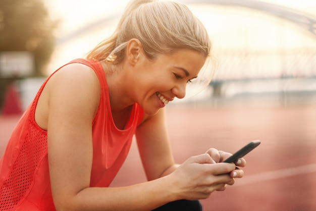 ポニーテールの美しいブロンドの女性のクローズアップとスマートフォンでメッセージを入力してスポーツウェアに身を包んだ。フィットネス屋外コンセプト。