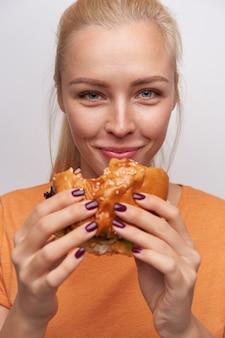 패스트 푸드를 먹고 유쾌하게 카메라를보고, 캐주얼 옷에 흰색 배경에 포즈를 취하는 동안 즐겁게 웃고있는 아름다운 파란 눈의 젊은 금발의 여자의 근접