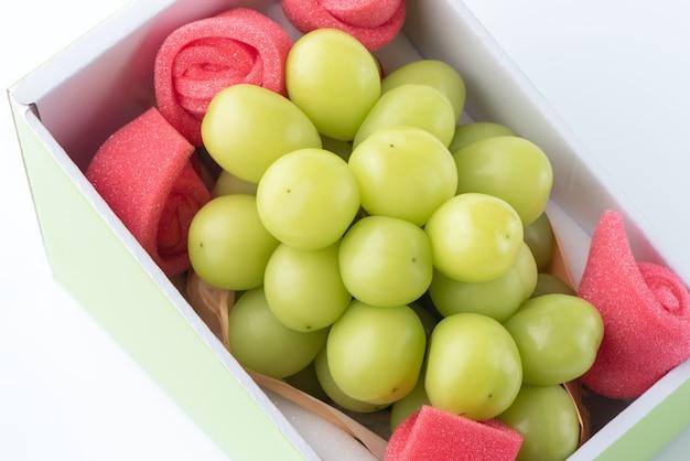 白で隔離される美しい箱入りの神社マスカット緑ブドウのクローズアップ