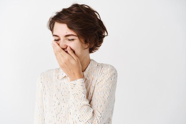 블라우스를 입은 아름다운 갈색 머리 여성 클로즈업, 농담으로 웃으면서 입을 가리고 흰 벽에 기대어 서 있다