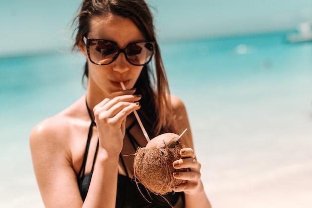 Закройте вверх красивого брюнет в купальнике и солнечных очках выпивая коктеиль пока стоящ на пляже.