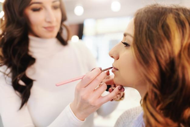 메이크업 아티스트가 그녀의 입술에 립스틱을 넣어 동안 미용실에 앉아 아름 다운 백인 갈색 머리의 닫습니다.